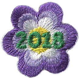A purple flower with six petals and a yellow center. The date '2018' rests in the middle of this one inch flower.