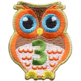 An orange owl with big blue eyes stands at the ready. The number ''3'' is embroidered in green on the owl's chest.