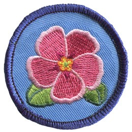 This merrow bordered circle badge has a pink primrose in the center with two green leaves peeking out.
