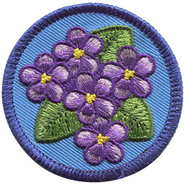 This circular patch displays a bunch of violets (6 flowers) sitting amongst a triangle of green leaves.