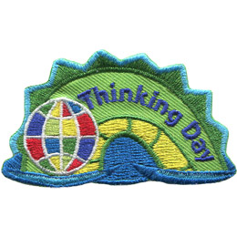 The middle hump of a sea serpent. The words 'Thinking Day' are embroidered along the middle of the hump. A multi-coloured globe rests on the left most section of the hump.
