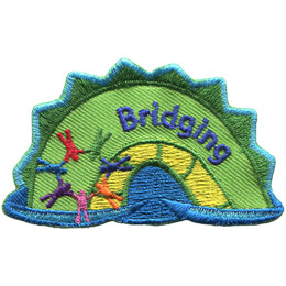 The middle hump of a sea serpent. The word 'Bridging' is embroidered along the middle of the hump. A rainbow ring of people connected at the hands rests on the left most section of the hump.
